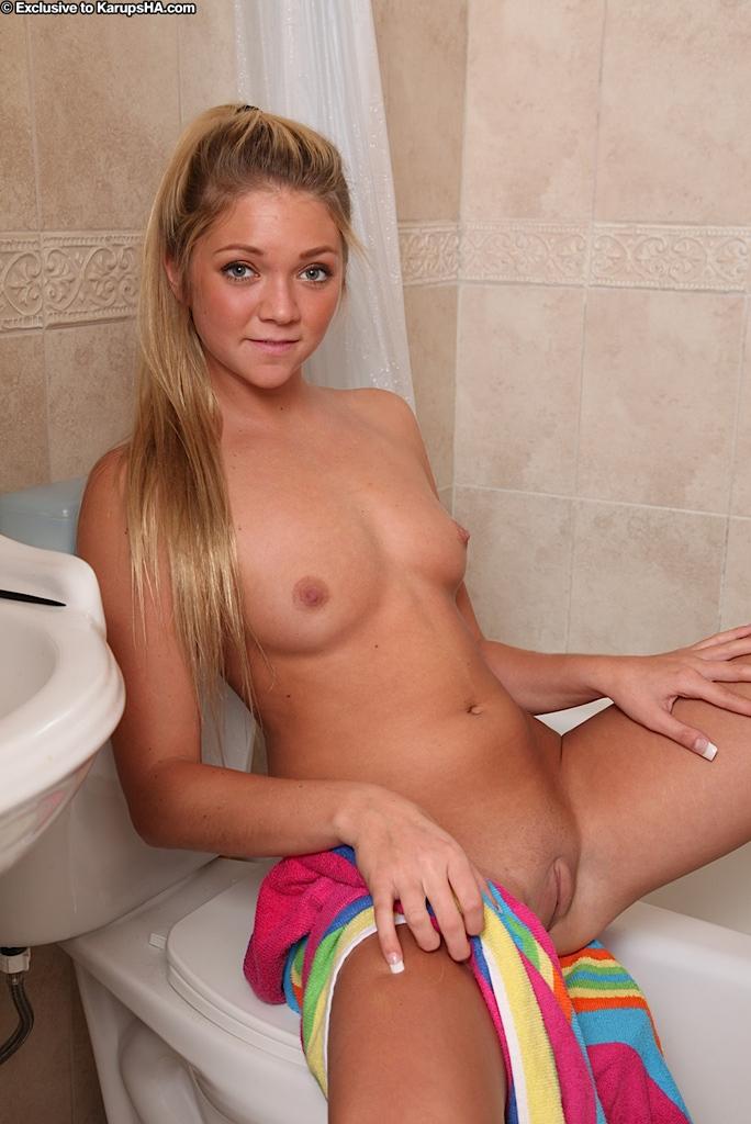 Блондинка с маленькой грудью показывает тело возле белой ванны