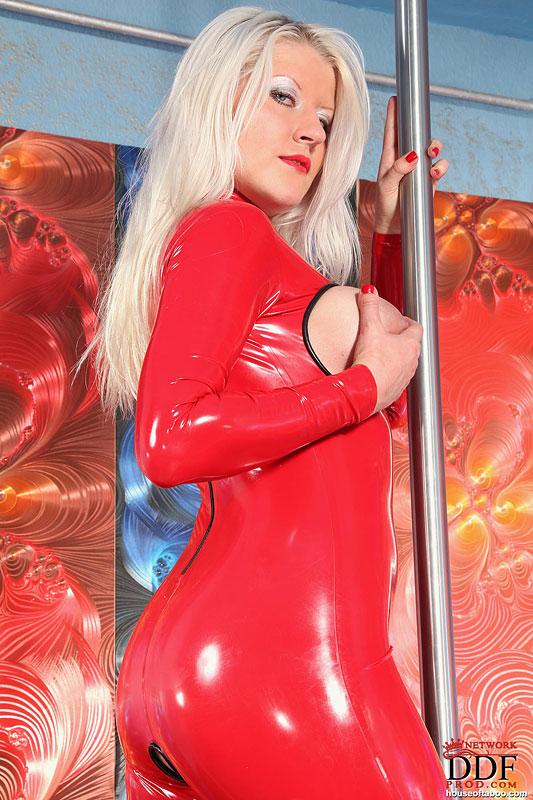 Блондинка в красном латексном наряде садится на фаллос возле пилона