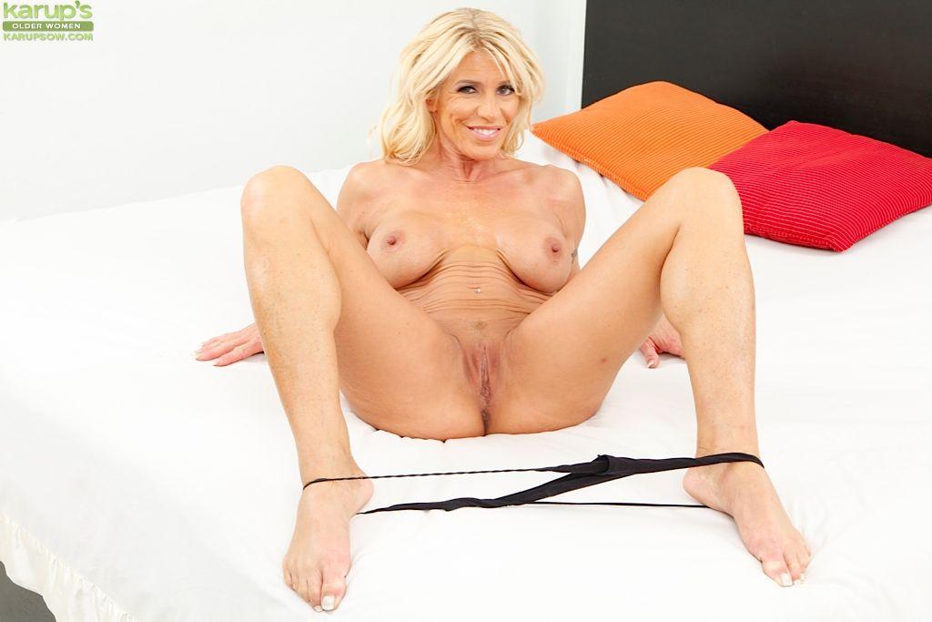 Соблазнительная мамочка-блондинка Gina West показывает большую грудь и бритую зрелую киску на кровати
