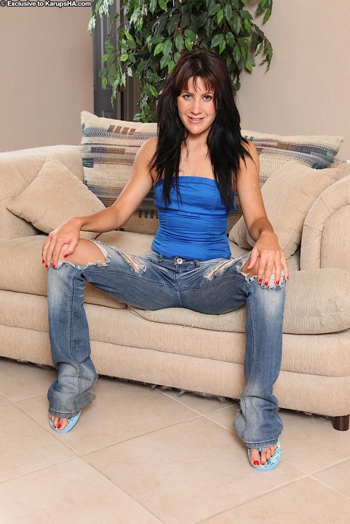 Девушка с бритой киской Lina Paige снимает джинсы и трусики