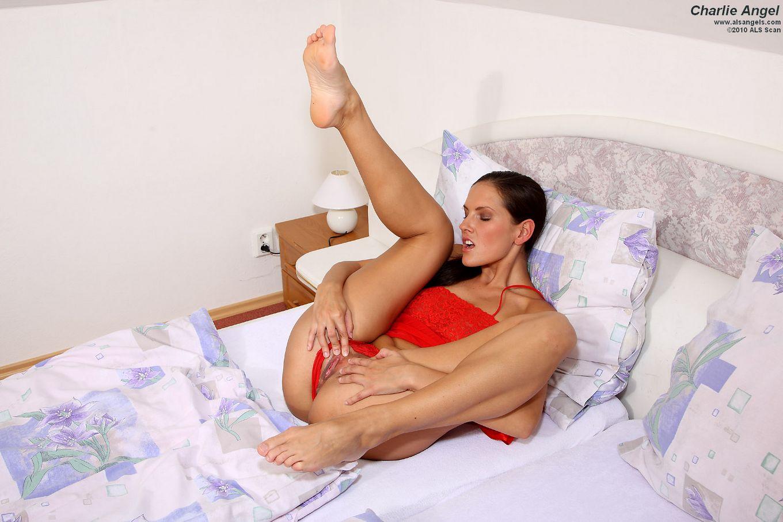 Длинноногая брюнетка Zuzana P снимает красное нижнее белье и играет с своей лысой киской в кроватке